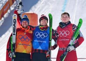 男子スキークロス決勝で優勝したカナダのブレイディー・リーマン(中央)。左は2位のマルク・ビショフベルガー、右は3位のセルゲイ・リジク(21日、平昌)=共同