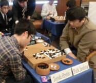 世界学生囲碁王座戦の優勝決定戦を制して優勝した韓国の朴才東さん(右)。左は準優勝の豊田裕仁さん(21日、東京都中央区)