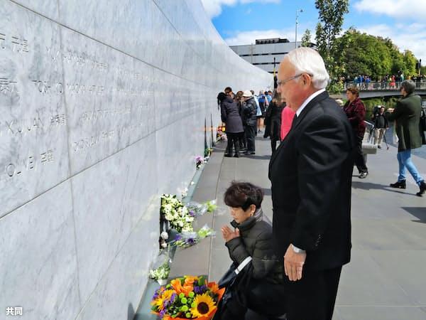 ニュージーランド地震から7年の追悼式典で、慰霊碑に献花する鈴木陽子さんの父、喜久男さん(右)と妻の千鶴子さん(22日、クライストチャーチ)=共同