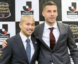 Jリーグ開幕前日の記者会見で、肩を組んで写真撮影に応じる鳥栖・吉田(左)と神戸・ポドルスキの両選手(22日、ベアスタ)=共同