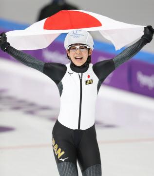 女子マススタートで金メダルを獲得し、日の丸を掲げる高木菜選手(24日、江陵)=上間孝司撮影