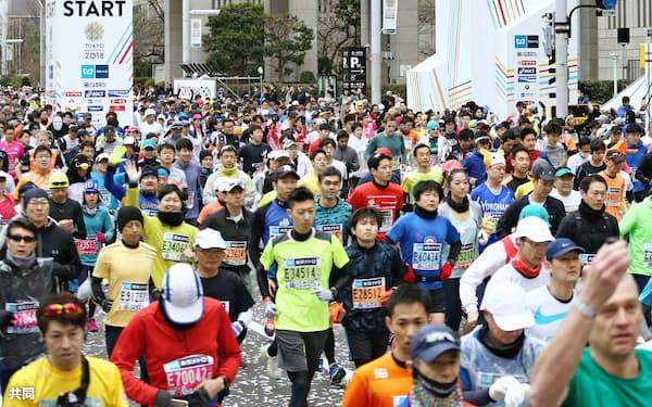 東京マラソンで都庁前をスタートするランナー(25日、東京・西新宿)=共同