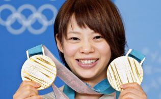 スピードスケート女子の団体追い抜きとマススタートで獲得した二つの金メダルを手に笑顔の高木菜那選手(25日、韓国・平昌)=共同