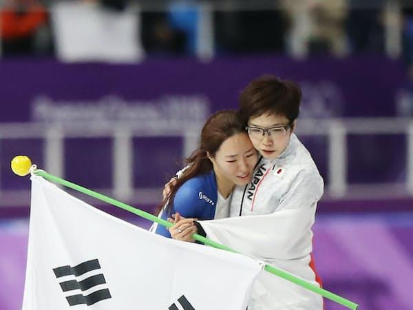 金メダル獲得後、2位だった韓国の李相花選手(左)と抱き合う小平選手(18日、江陵)=上間孝司撮影