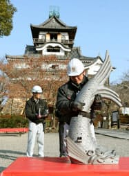国宝犬山城天守(後方)北側に取り付けられる新しいしゃちほこ(26日午前、愛知県犬山市)=共同