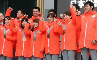 帰国報告会に登壇して聴衆の声援に応えるカーリングの選手ら(27日午前、東京都港区)