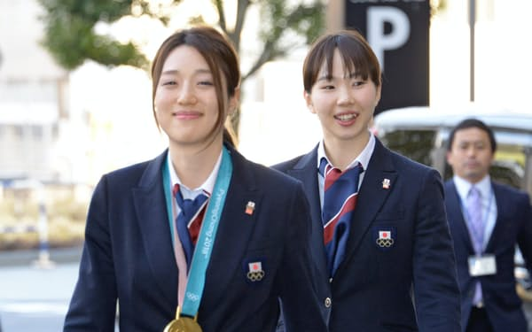 金メダルを胸に山梨県庁に入る菊池彩花さん(左)と押切美沙紀さん(27日、甲府市)
