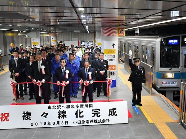 小田急線の複々線化が完成し下北沢駅を出発する一番列車と、開通式でテープカットする関係者(3日午前、東京都世田谷区)
