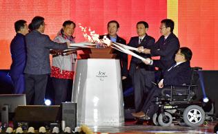 平昌冬季パラリンピックの開幕を前に、各都市で採火された聖火を一つにする関係者(3日、ソウル)=共同
