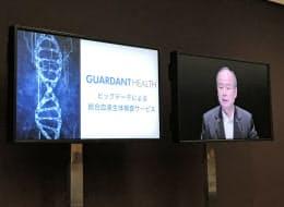 ソフトバンクの孫正義社長(右)は株主総会で、投資先ベンチャーの高い技術を紹介した(21日午前、東京・丸の内)=テレビモニターより