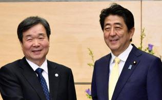 BIEの崔在哲調査団長(左から4人目)と握手する安倍首相(6日午後、首相官邸)=共同