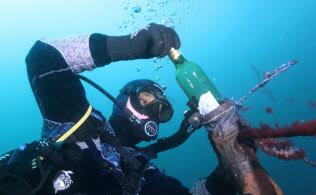 ホタテ養殖のロープに地元産の白ワインのボトルをつるし、海中の揺らぎによる熟成を試みる漁師でダイバーの佐々木淳さん(岩手県大船渡市の越喜来湾)