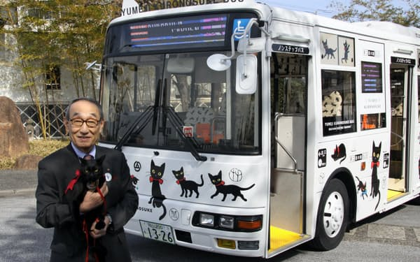 バスの前に立つ岡山電気軌道の小嶋社長(7日、岡山市)