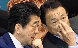 参院予算委の開会前に、話し込む安倍首相(左)と麻生財務相(8日)=共同