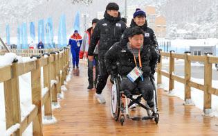 選手村に設置されたスロープを移動する韓国の選手ら(8日、平昌)=横沢太郎撮影