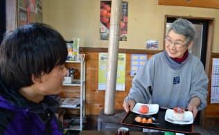 特産のカキを使った菓子を提供する藤井サヱ子さん(右)(2月26日、岩手県釜石市)