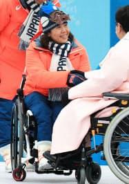 入村式で選手村村長(右)と握手する、大日方団長(6日、平昌)=横沢太郎撮影