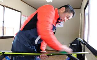 ワックスを塗ったスキー板にブラシをかける佐藤勇治さん(1月22日、札幌市)