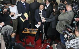 国税庁長官を辞任し、記者の質問に答える佐川氏(中央)=9日午後、財務省
