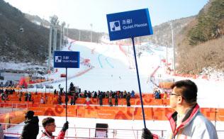 アルペンスキーの会場で、観客席に「静かに」と書かれた看板を掲げるボランティア(11日、平昌)=西城彰子撮影