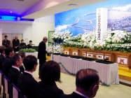 港町だった震災前の写真を掲げた祭壇に向かって語りかける、福島県浪江町の馬場有町長(11日)