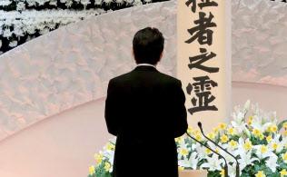 政府主催の追悼式で、祭壇に向かい式辞を述べる安倍首相(11日午後)=共同