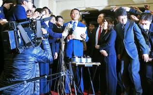 記者の質問に答える麻生財務相(中)(12日午後、財務省)