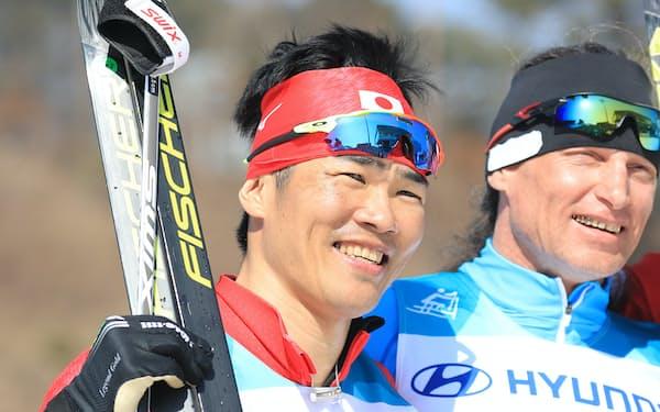 男子スプリント・クラシカル立位で銀メダルを獲得し笑顔の新田(左)=横沢太郎撮影