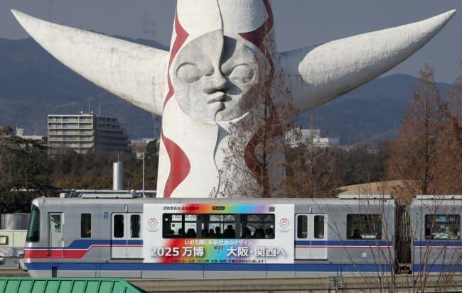 大阪モノレールのラッピング列車「2025万博誘致号」が、太陽の塔の前を横切った