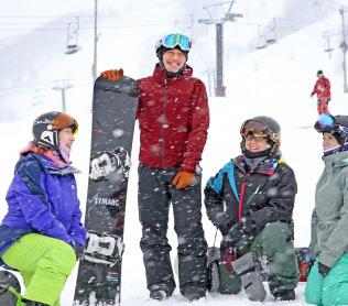 障害者スノーボード滑走会の参加者と談笑する二星さん(左から2人目)=2月12日、長野県小谷村