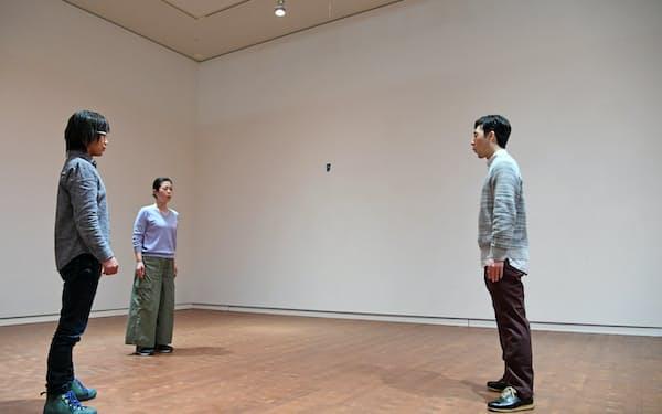 つり下げた石に息や口笛を吹くアローラ&カルサディーラのパフォーマンス「Lifespan」(大阪市北区の国立国際美術館)