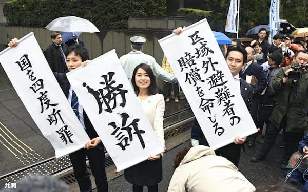 福島第1原発事故で自主避難した住民らの訴訟の判決で垂れ幕を掲げる原告側弁護士(16日、東京地裁)=共同