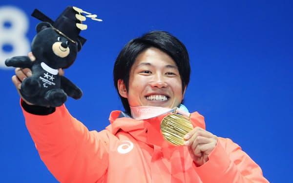 スノーボードバンクドスラローム男子下肢障害で金メダルを獲得し、表彰式で笑顔を見せる成田=横沢太郎撮影