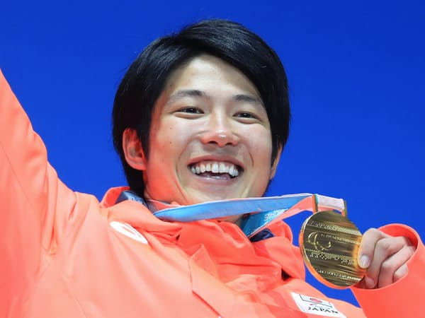 表彰式で金メダルを手に笑顔の成田=横沢太郎撮影