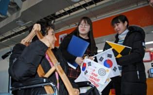 アイスホッケー会場で車いすの観客に話を聞く上智大生(江陵)=西城彰子撮影