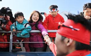 金メダルを獲得した新田佳浩選手(手前)と握手する妻の知紗子さん(17日、平昌)=横沢太郎撮影