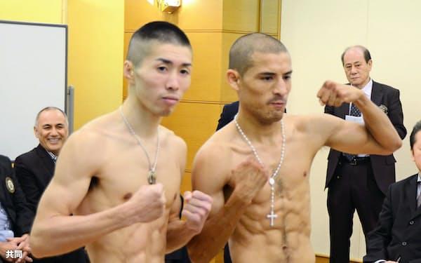 WBOミニマム級世界戦の前日計量をパスし、ポーズをとる山中竜也(左)とモイセス・カジェロス(17日、神戸市)=共同