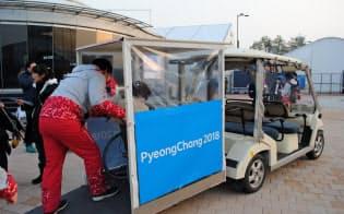 会場内でゴルフカートを改造した乗り物に乗り込む車いすの女性(江陵)=西城彰子撮影
