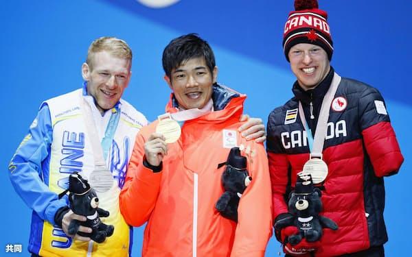 スキー距離男子10キロクラシカル立位のメダル授与式で金メダルを手に笑顔の新田佳浩(中央)。左は銀のウクライナのグリゴリー・ボウチンスキー、右は銅のカナダのマーク・アレンズ(17日、韓国・平昌)=共同