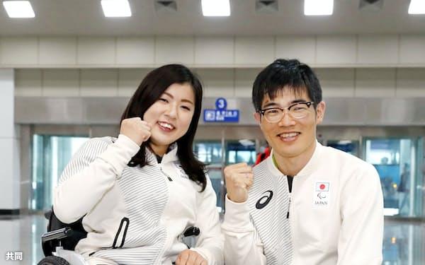 帰国のため、韓国東部の襄陽空港に到着し笑顔で撮影に応じる、アルペンスキー女子の村岡桃佳選手(左)とスキー距離男子の新田佳浩選手(19日)=共同