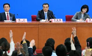 20日、中国全人代が閉幕し、北京の人民大会堂で記者会見する李克強首相(中央)=共同