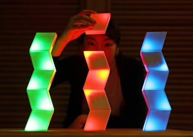ひし形の照明機器を近づけると、光が同期して同じ色が広がっていく(大阪市北区)