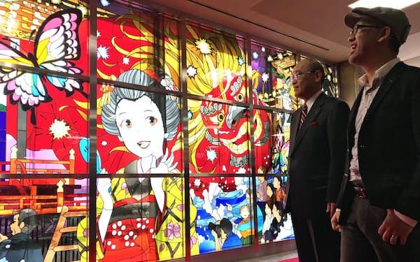 小松空港に登場したステンドグラスを眺める米林宏昌監督(右)と石川県の谷本正憲知事(22日、小松市)