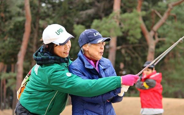 レッスンプロ(左)の指導を受けてゴルフを楽しむ高齢者