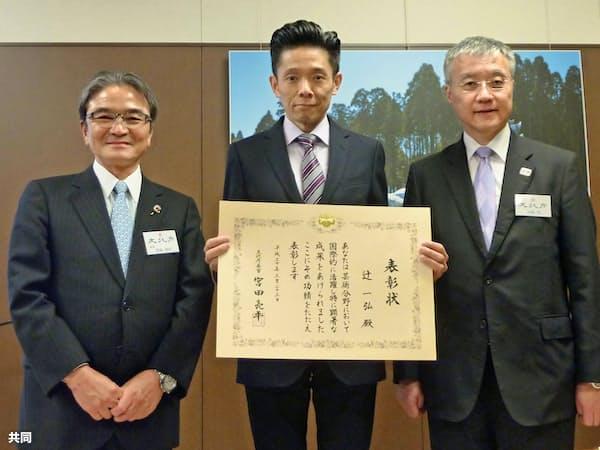 宮田長官(左)から表彰を受ける辻さん(中)(23、文化庁)
