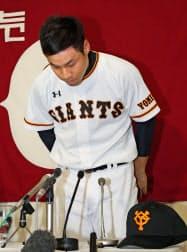 支配下選手登録され、記者会見で頭を下げる巨人の高木京介投手(23日、東京ドーム)=共同