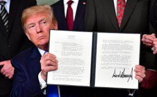 米首都ワシントンで中国製品への制裁措置を指示する大統領令に署名後、掲げるトランプ米大統領(22日)=UPI共同