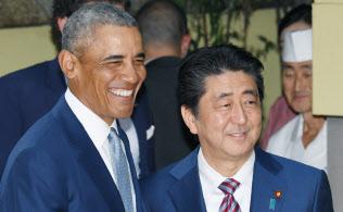会食の前にオバマ前米大統領(左)と握手する安倍首相(25日午後、東京都中央区)