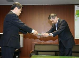 石井国交相(左)から指示文書を受け取る日産自動車の西川広人社長(26日午前、国交省)