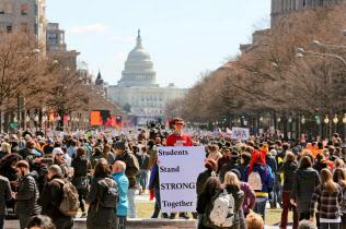 3月24日、米首都ワシントンで、銃規制強化を求めるデモ参加者ら。中央のプラカードには「生徒は団結し断固とした姿勢を取る」と書かれている=共同